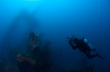 Underwater photographer exploring wreck ship in the deep.