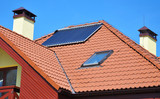 Energy efficiency concept. Closeup of solar water panel heating on red tiled house roof with lightning protection, skylights, chimney and roof window