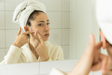 Woman with acne problem looking to mirror