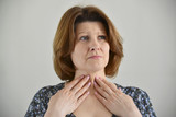 Adult woman with a sore throat on  light background