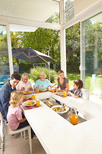 Family in three generations eating at lunch table Poster