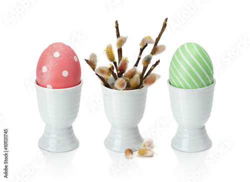 Naklejka Colorful easter eggs in egg cup, with pussy-willow. Isolation on a white background