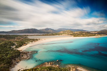 View of a beautiful bay with azure sea from top of a hill, Villasimius, Sardinia island, Italy, with a long exposure to move the clouds and to silk the sea