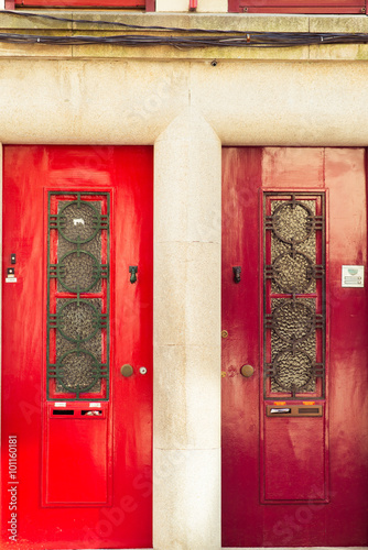 Red wooden glass door of a red brick classical building © Aleksey Zakharov