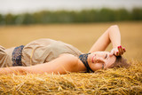 Молодая красивая девушка лежит на стоге сена