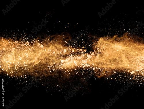 Explosion of orange powder on black background