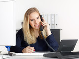 Fototapety Female office assistant has a call at the office