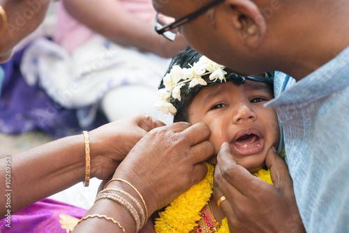Foto op Canvas Bedehuis Baby girl crying in Hindus ear piercing ceremony