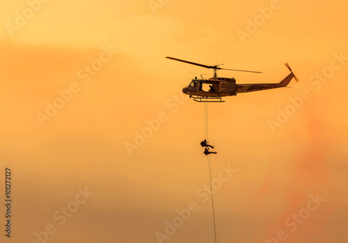 obraz lub plakat soldiers climb down from helicopter in military mission.