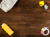 disposable diaper, teether, dummy, baby powder and rubber duckling on dark wooden background with copy-space. Flat lay