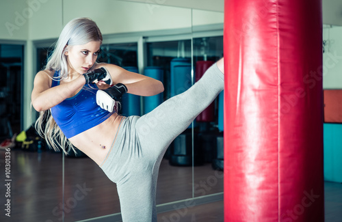 obraz lub plakat Woman hits the heavy bag with a strong kick