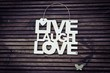 Metal sign with the words LIVE LAUGH LOVE with a metal butterfly on a wooden surface