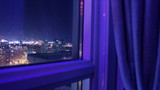 Night Window City Timelapse Slider. Time lapse shot on a motion slider pushing out towards a high-rise window overlooking a night city skyline.