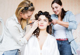 Fototapety Stylist and makeup artist preparing bride before the wedding in a morning