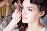 Fototapety Make-up artist preparing beautiful bride for ceremony in a morning
