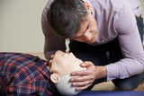 Man In First Aid Class Checking Airway On CPR Dummy