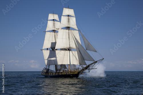 Keuken foto achterwand Schip Tall ship with cannons firing sailing on blue waters