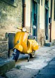 Yellow scooter in tuscan Cortona town
