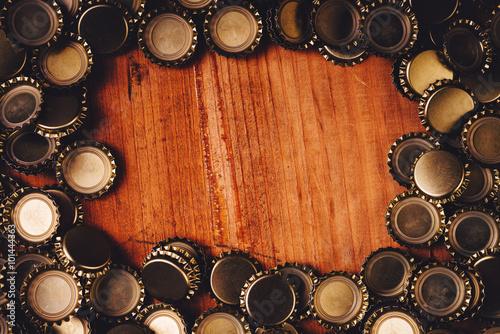Beer bottle caps frame over wooden background