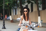 Young beautiful woman sitting on a scooter.