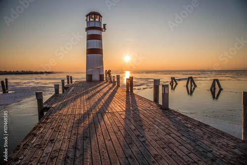 Holzsteg mit Leuchtturm im Winter vor gefrorenem See im Sonnenuntergang - 101468585