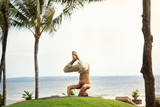 Muscular healthy man doing yoga in tropical nature