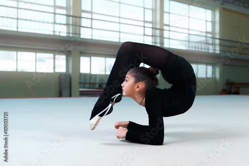 Poster gymnast performs a back bend on  floor