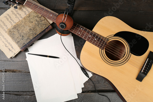 Staande foto Muziekwinkel Acoustic guitar, headphones, musical notes and white papers on wooden background, close up