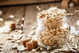 Sweet puffed rice with caramel in a glass jar on the old wooden