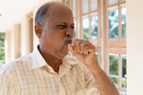 Closeup portrait, old man coughing with post nasal drip bug, really sick in bad weather, holding fist to mouth, isolated outdoors outside background