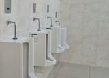 white porcelain urinals in public toilets - 101575720