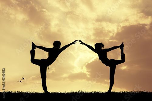 Poster couple doing yoga at sunset