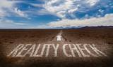Reality Check written on desert road