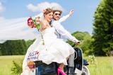 Fototapety Hochzeit Bräutigam und Braut fahren mit Motorroller und haben Spaß