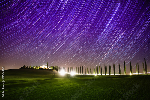 Foto op Canvas Violet Beautiful Tuscany night landscape with star trails on the sky, cypresses and shining road in green meadow. Natural outdoor amazing fantasy background.