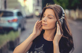 Young Caucasian brunette woman with headphones outdoors on sunny summer day