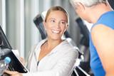 Fototapety Fitnesstrainer hilft Senior am Laufband