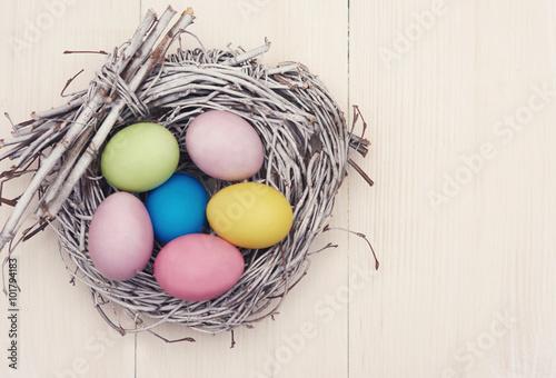 Fototapeta Wicker nest full of multi colored eggs.