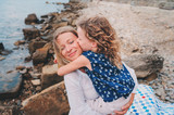 portrait of happy mother and daughter spending time together on the beach on summer vacation. Happy family traveling, cozy mood. Child kissing mother.