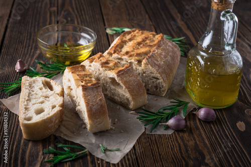 Sliced italian bread Ciabatta with rosemary on wooden background плакат