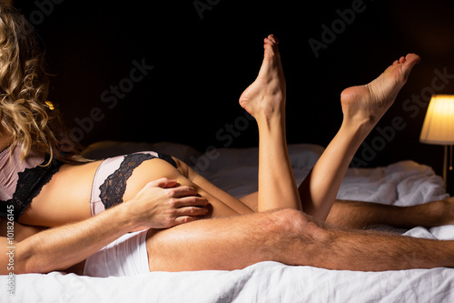 Woman lying on top of man in bedroom  - 101826145