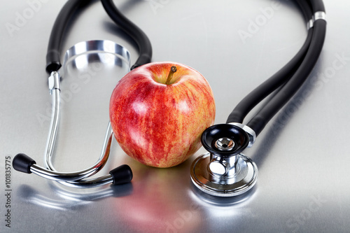 Fresh red apple and stethoscope on stainless steel