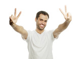 young casual man showing the victory gesture