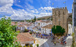 Obidos, Portugal. Cityscape of the town with medieval houses, wall and the Albarra tower. Obidos is a medieval town still inside castle walls, and very popular among tourists.