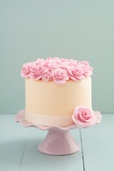 Ivory fondant covered cake with pink sugar roses on cake stand