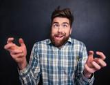 Fototapety Ugly bearded man grimacing over black background