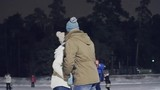 Happy young couple enjoying ice-skating and kissing at outdoor skating rink at night
