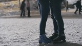 Low section of couple in ice skates hugging at outdoor skating rink, girl standing on tiptoes to kiss her boyfriend