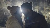 Happy couple laughing and kissing in the street light at snowy winter night