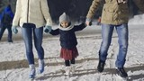 Adorable little girl enjoying ice skating with her parents at outdoor rink in park